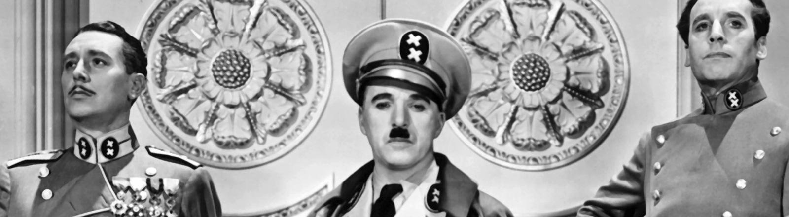 """Filmszene aus """"Der große Diktator"""". Charlie Chaplin trägt Uniform und steht zwischen zwei Männern, ebenfalls in Uniform; Bild: dpa"""