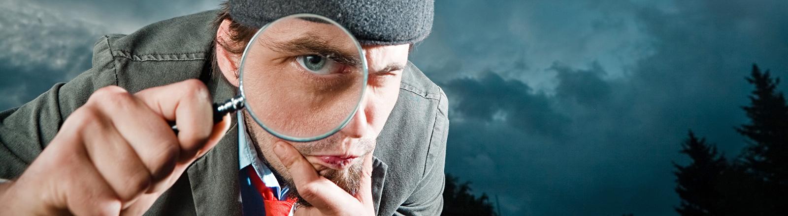 Ein Mann hat eine Lupe vor dem Auge und blickt hindurch. Er macht einen nachforschenden Eindruck.
