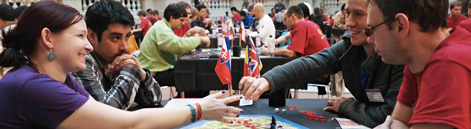 An einem Tisch sitzen drei junge Männer und eine junge Frau. Auf dem Tisch ein Brettspiel. Die Frau und einer der Männer reichen sich eine Spielkarte über den Tisch; Bild: dpa | Jörg Carstensen