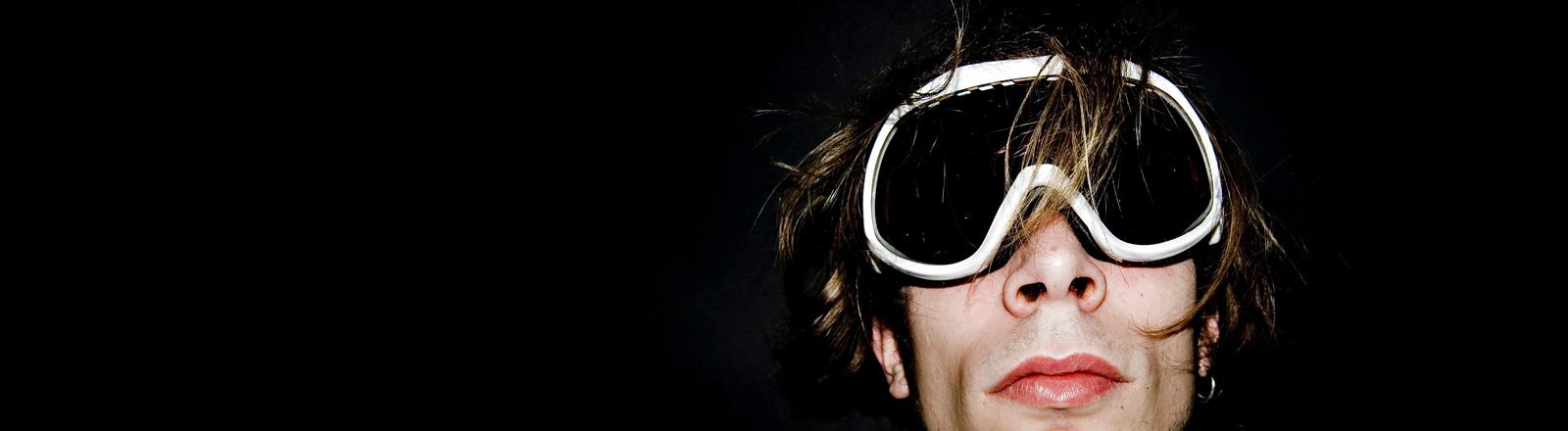 Ein Mann trägt eine schwarze Skibrille. Nur sein Kopf ist zu sehen, der Bildhintergrund ist schwarz.
