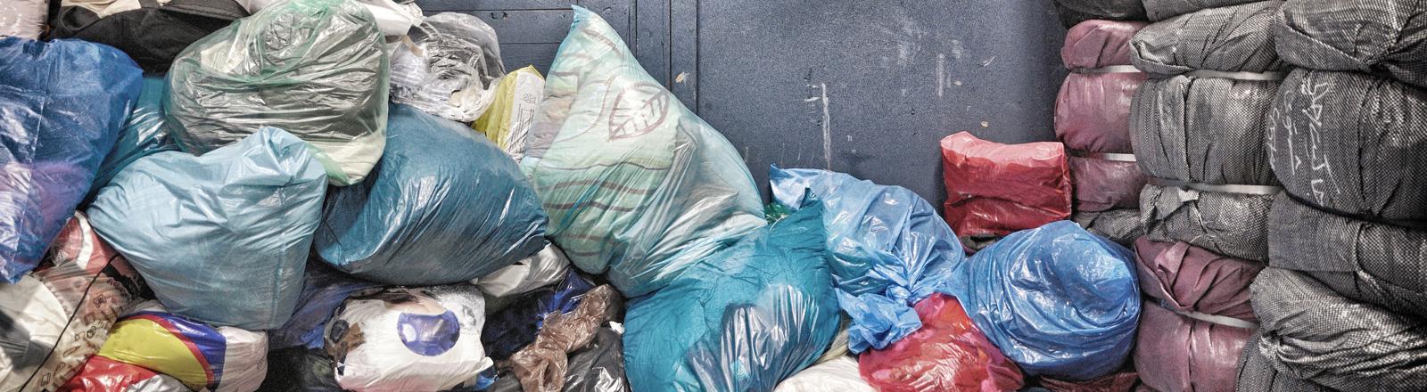 Ein Haufen bunter Müllsäcke, die übereinander liegen. Teils kann man Kleidung in den Säcken erkennen.