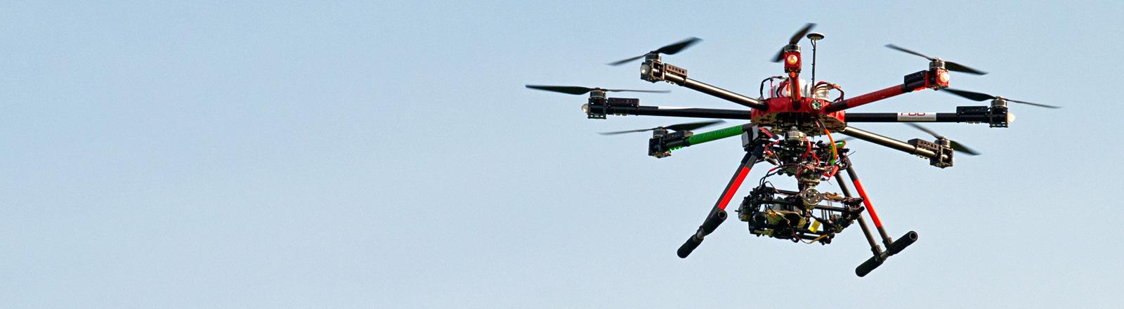 Ein Quadrokopter mit acht Rotoren schwebt am Himmel; Bild: dpa