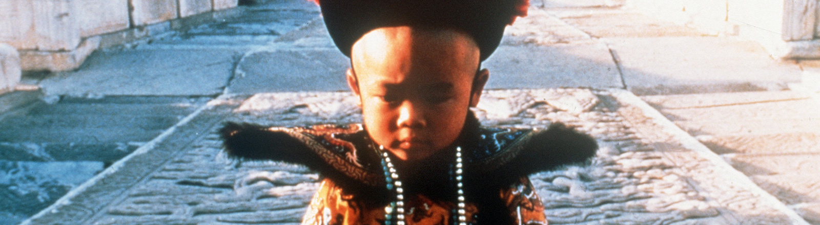 """Filmszene aus """"Der letzte Kaiser"""", zeigt einen kleinen jungen in festlicher Kleidung; Bild: dpa"""