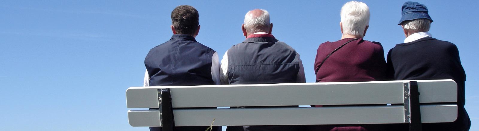 Vier Männer und Frauen sitzen auf einer Bank, sie haben teils graue Haare. Sie sind von hinten zu sehen.