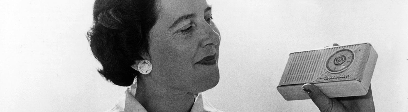 Schwarz-Weiß-Foto. Eine Frau hält ein Transitorradio in der Hand. Es ist etwa so groß wie eine Schokolade, aber dicker. Die Aufnahme ist von 1957; Bild: dpa