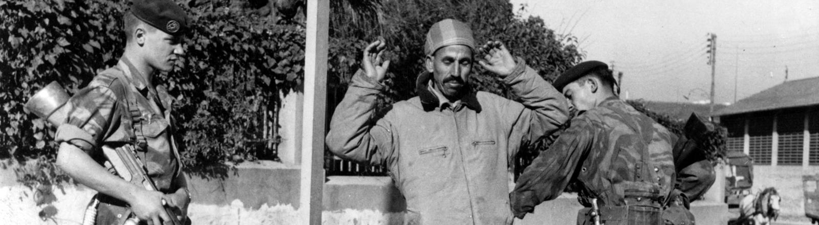Französische Fallschirmspringer halten 1957 auf offener Straße in Algier einen Mann auf, befragen ihn und durchsuchen ihn nach Waffen.