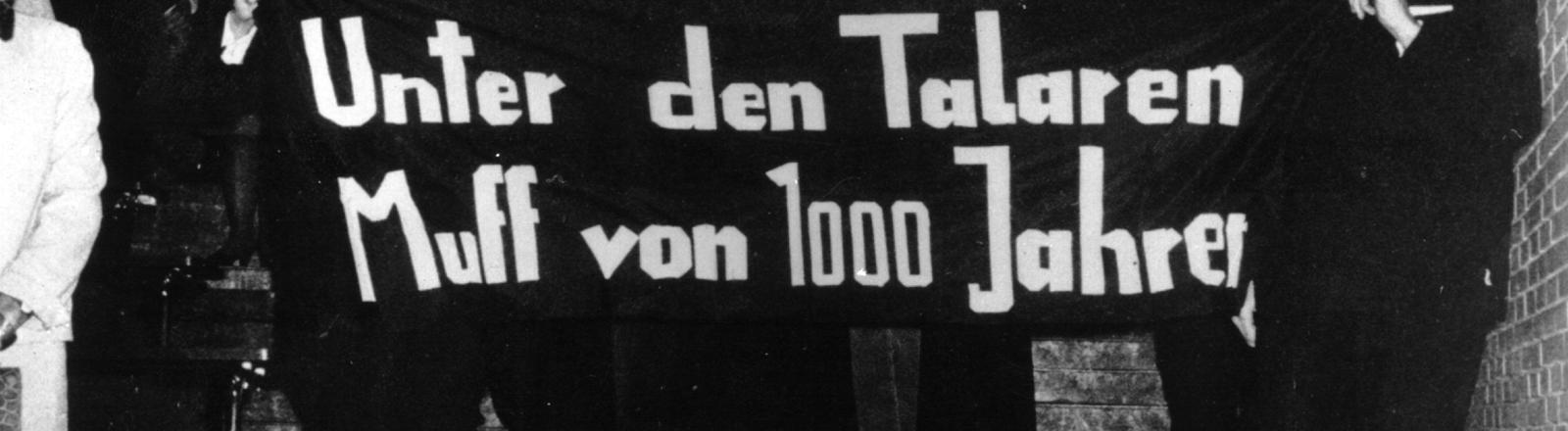 """""""Unter den Talaren - Muff von 1000 Jahren"""" steht auf dem Transparent, das Studenten am 09.11.1967 beim Eintritt des neuen und des alten Rektors der Universität Hamburg ins Auditorium Maximum halten."""