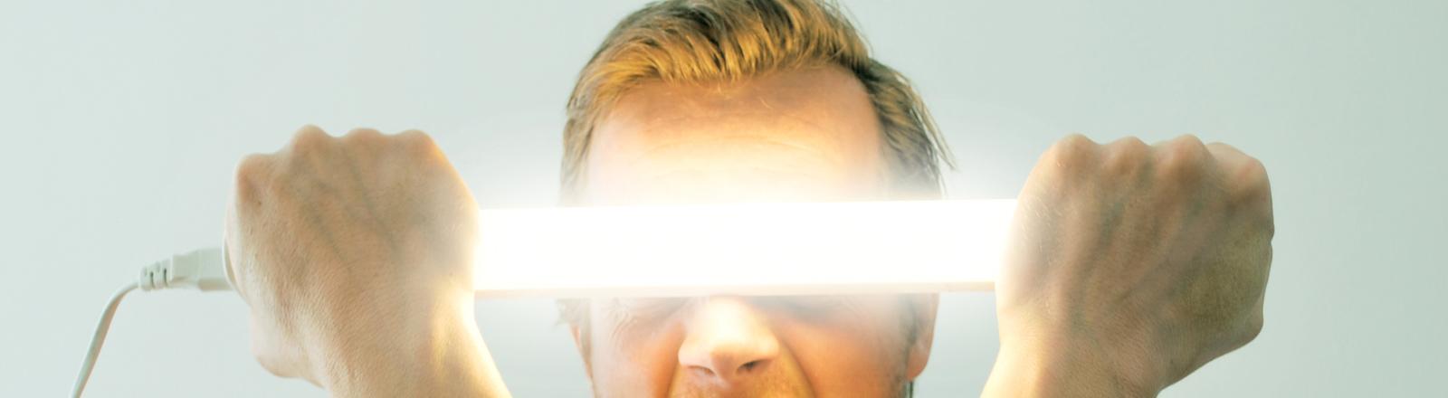 Die Macht der Gedanken... Ein Mann hält sich eine Neonröhre vor die Augen.