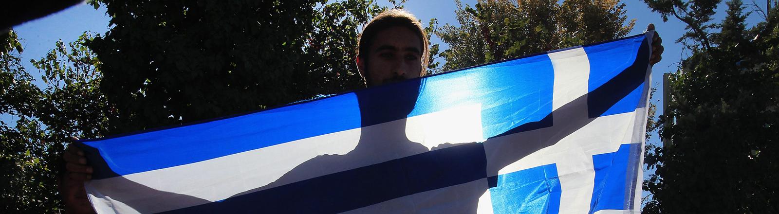 Ein junger Roma hält die griechische Flagge während er am 1. Oktober 2014 gegen die Zerstörung eines Roma-Lagers protestiert.