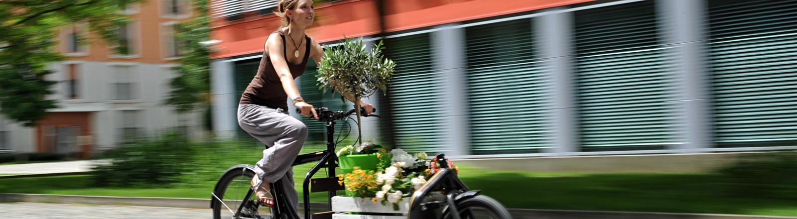 Eine Frau fährt in München mit einem Transportrad, auf dem Blumen stehen. Die Frau ist sommerlich gekleidet; Bild: dpa | Tobias Hase