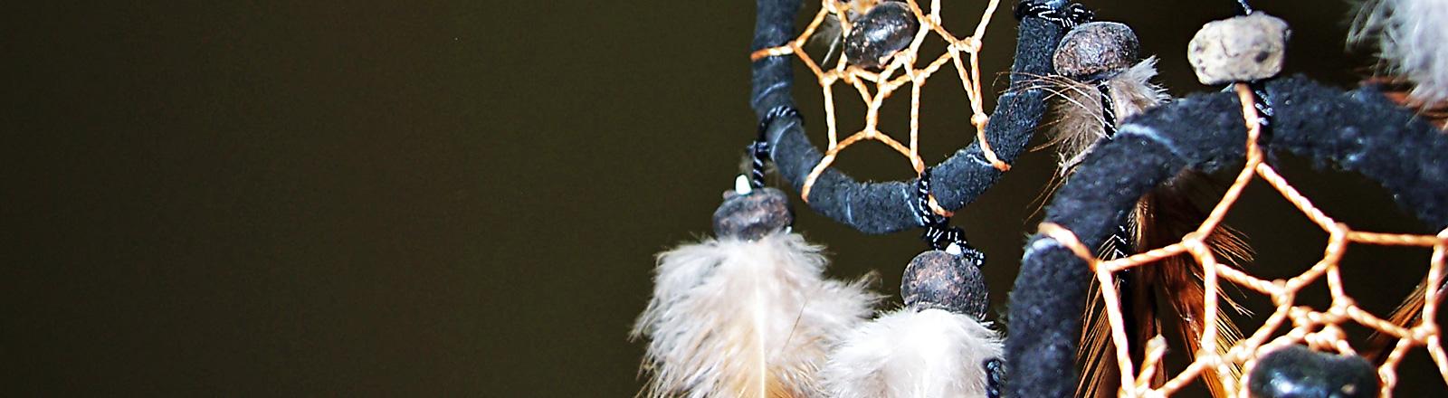 Rechts im Bild ist ein indianischer Traumfänger. An Ringen hängen Federn. In den Ringen sind Fäden gespannt.
