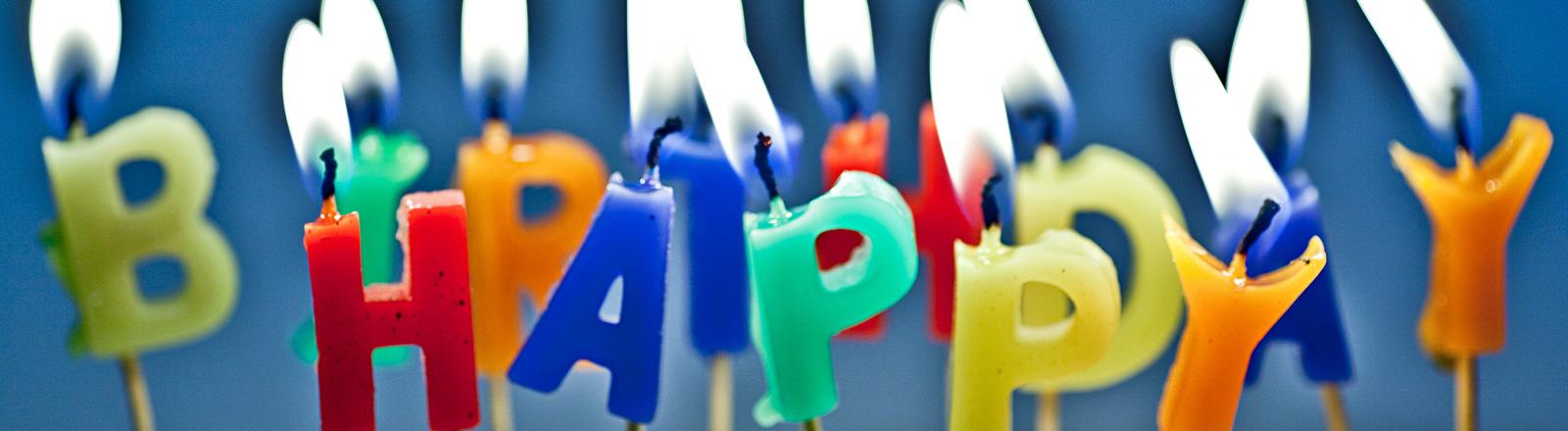 Bunte Kerzen in Buchstabenform stehen nebeneinander und brennen. Das Wort Happy ist zu lesen.