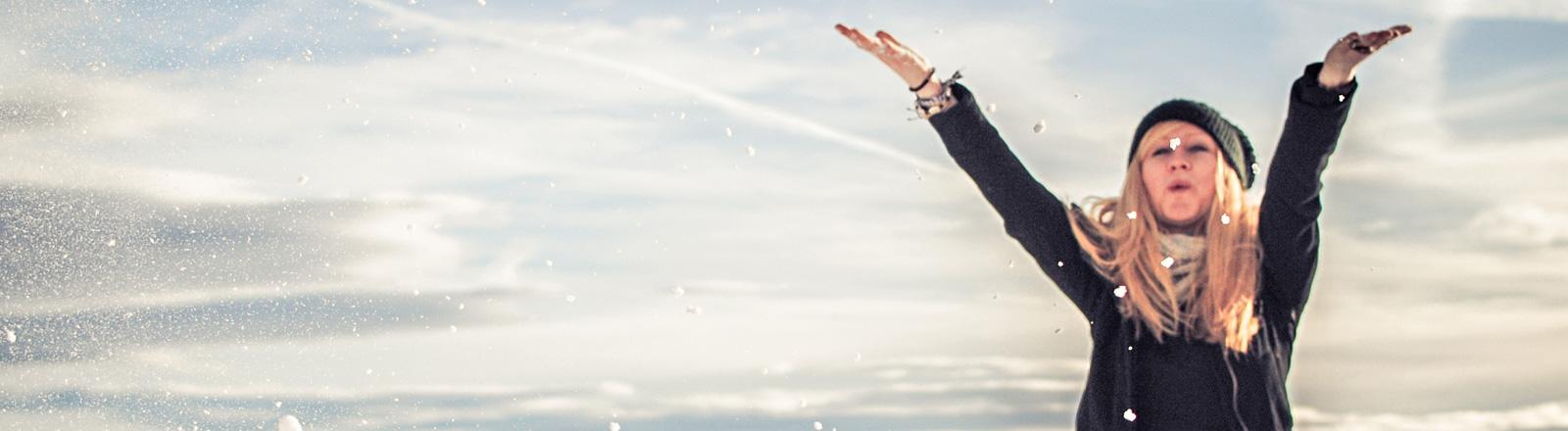 Eine Frau mit Jacke, Schal und Mantel hat die Arme in die Luft gehoben und schaut fröhlich. Sie steht vor einem Winterhimmel, es fällt Schnee.