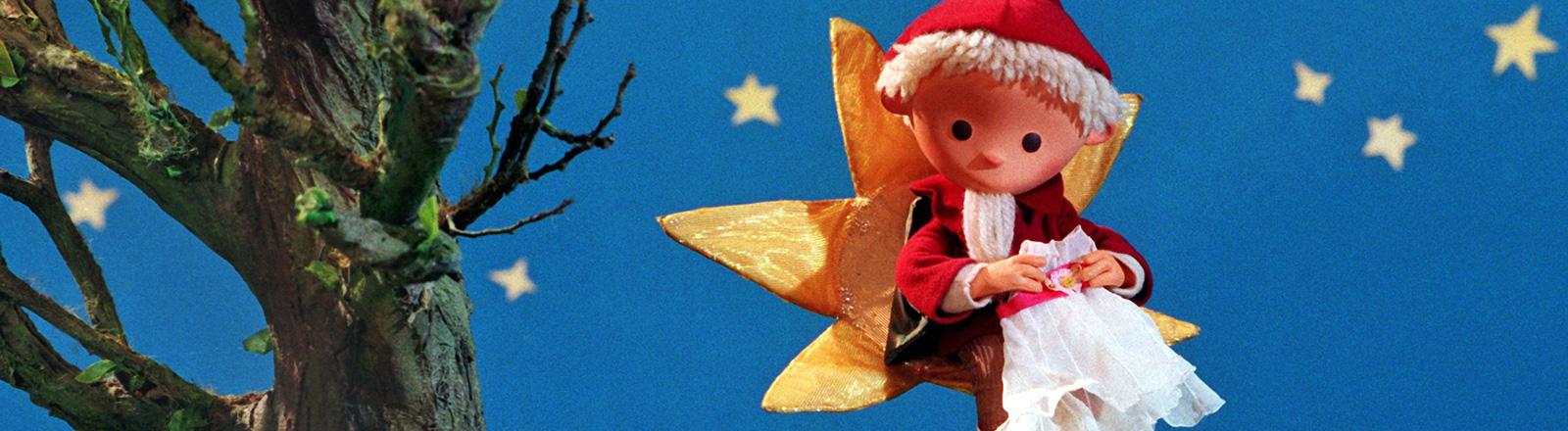Die Figur Sandmännchen sitzt auf einem Stern aus Stoff vor einer blauen Fläche mit Sternen. Links steht ein künstlicher Baum; Bild: dpa