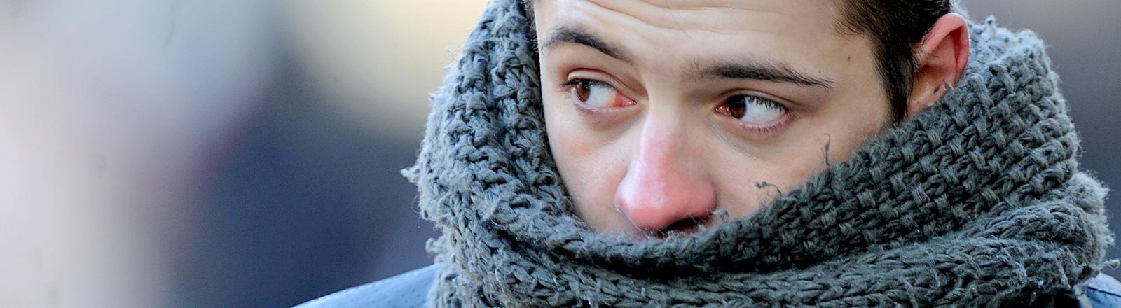 Ein Mann hat einen dicken Schal um seinen Hals gewickelt. Er hat eine gerötete Nase; Bild: dpa