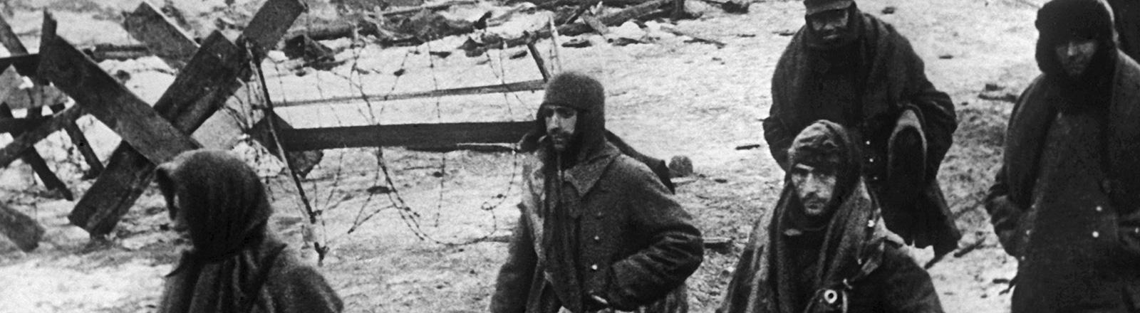 Schwarz-Weiß-Foto, deutsche Soldaten in Mänteln und mit Mützen verlassen nach der Kapitulation Stalingrad (undatiert); Bild: dpa