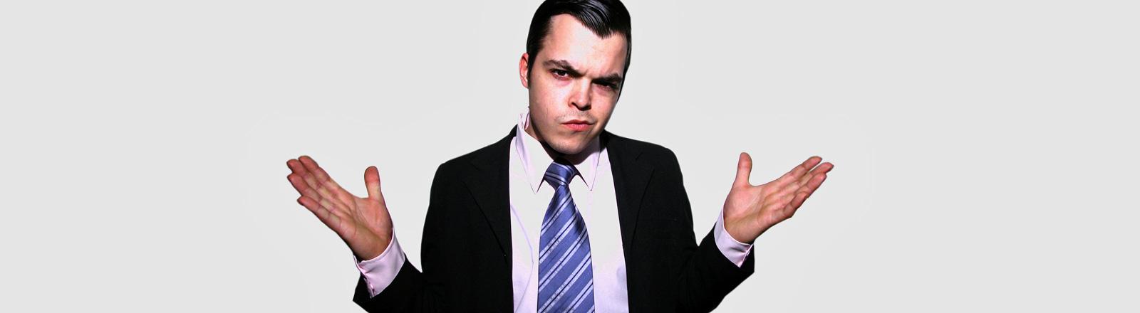 Ein Mann in Anzug und mit Krawatte hat den rechten Mundwinkel nach oben gezogen und hält die Hände geöffnet in die Höhe. Er wirkt herausfordernd und arrogant.