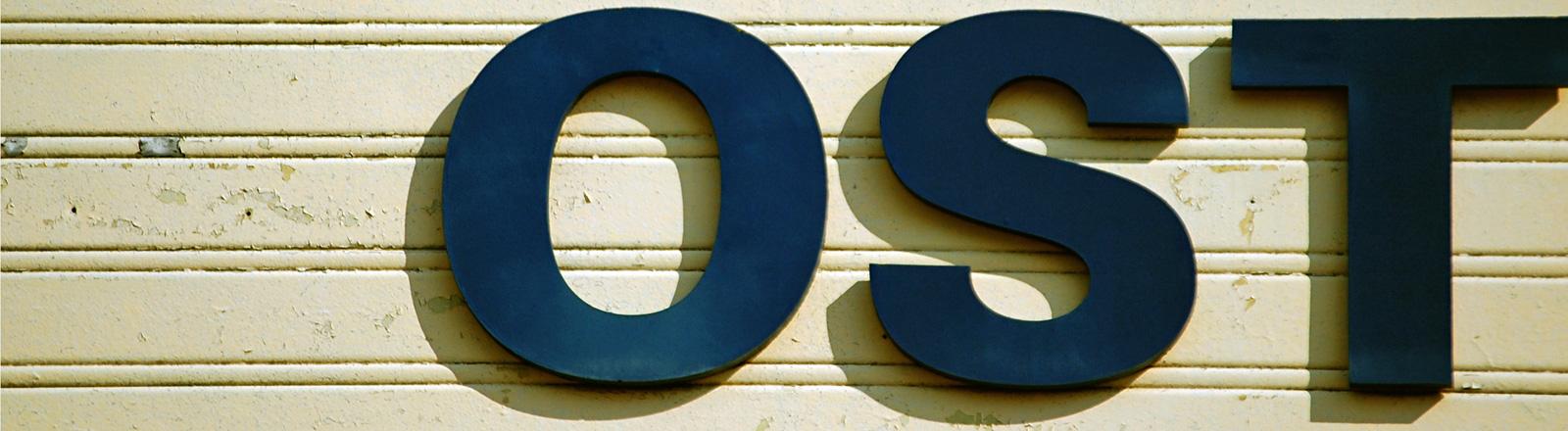 Die Buchstaben O, S und T hängen an einer Wand nebeneinander, also OST. Das P davor scheint zu fehlen.