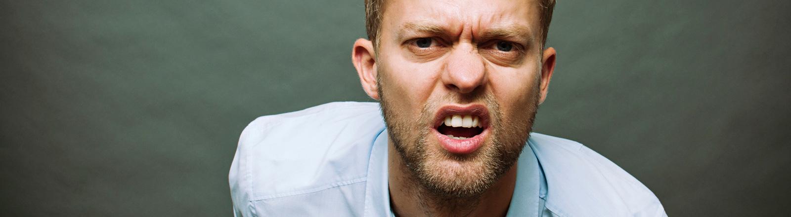 Ein junger Mann mit hellblauem Hemd blickt etwas blöde in die Kamera.