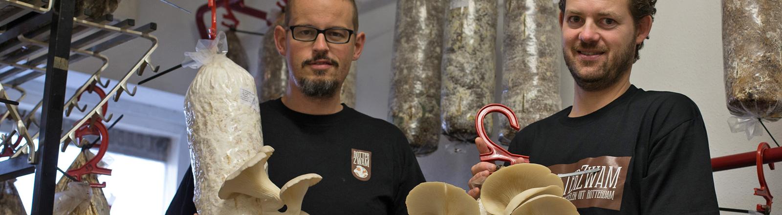 Siemen Cox und Mark Slegers stehen nebeneinander. Sie halten gefüllte Tüten in den Händen, aus denen Pilze seitlich herauswachsen.
