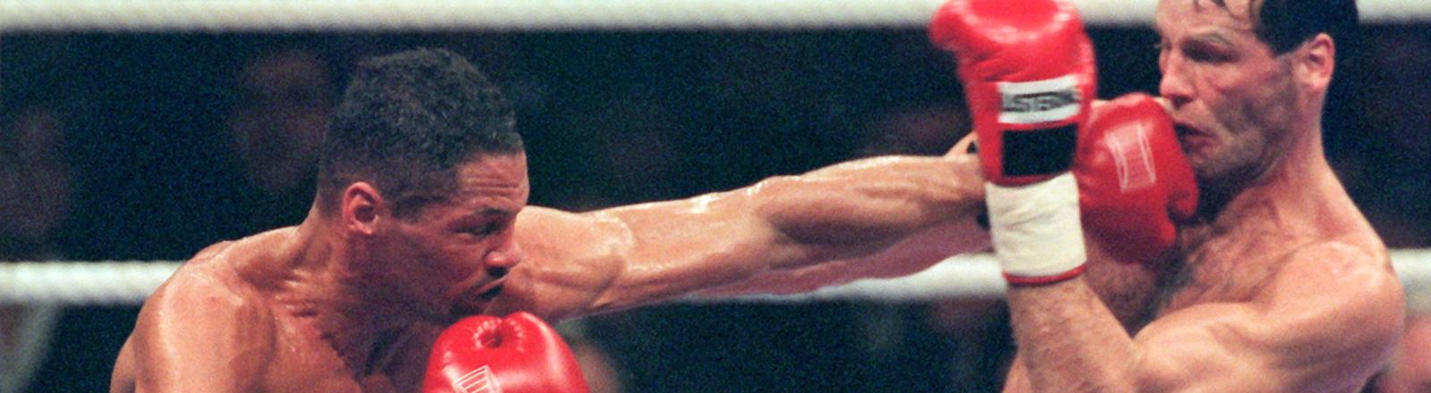 Henry Maske (rechts) und Virgil Hill (links) im Ring bei einem Boxkampf 1996. Hill schlägt mit einer linken Gerade durch die Deckung von Maske; Bild: dpa