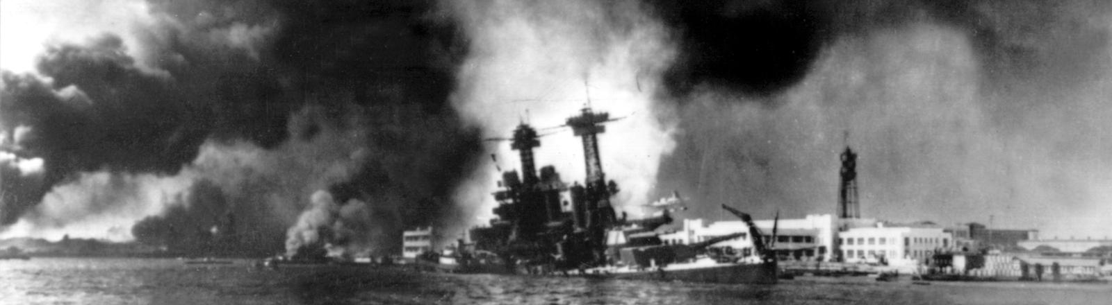 Blick auf brennende amerikanische Schlachtschiffe. Am 7. Dezember 1941 begann mit dem Luftangriff auf Pearl Harbor auf Hawaii.
