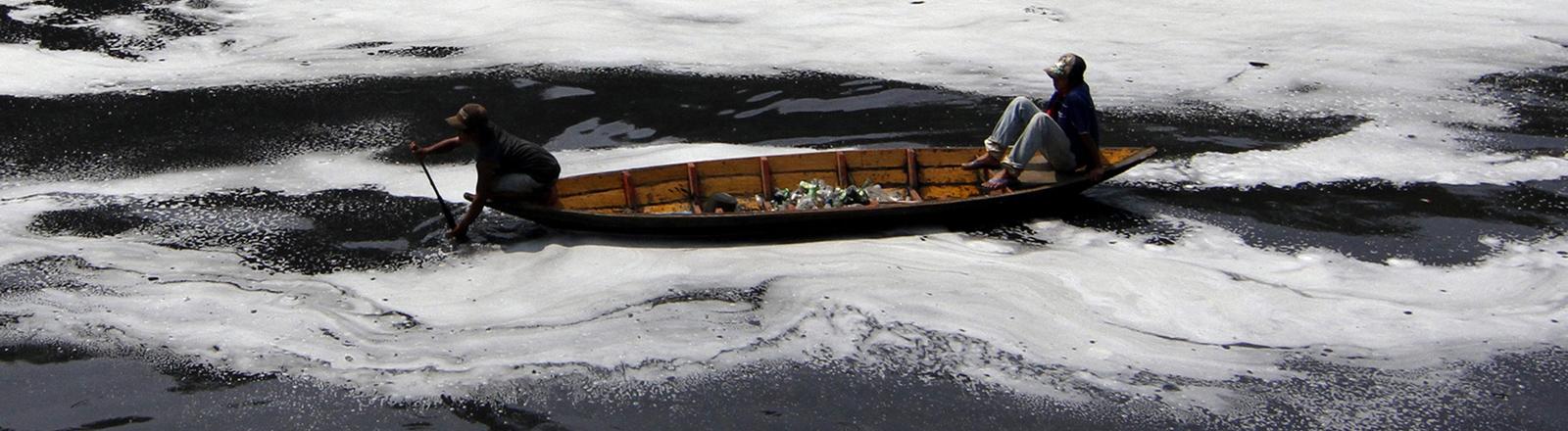 Zwei Männer sammeln mit ihrem Boot Plastikmüll aus dem Citarum-Fluss in Bandung in Indonesien.