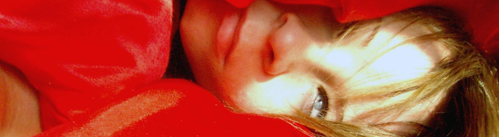 Eine Frau blinzelt unter ihrer roten Bettdecke hervor.