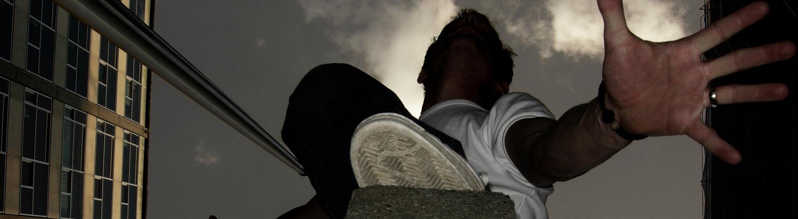 Ein Mann befindet sich in schwindelerregender Höhe.