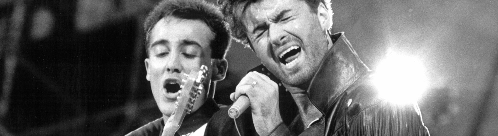 """Schwarz-Weiß-Foto, das britische Pop-Duo """"Wham"""" bei einem Konzert. Andrew Ridgeley an der Gitarre wird von George Michael umarmt, der die Augen geschlossen hält und in ein Mikrofon singt; Bild: dpa"""