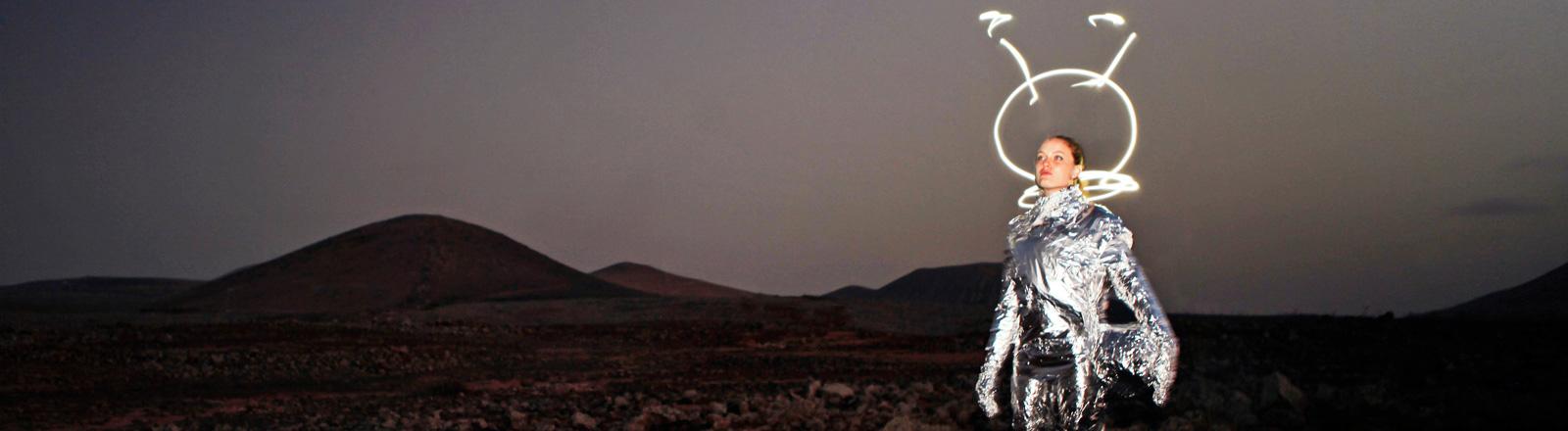 Eine Frau in Alupapier gehüllt steht vor einer kargen Landschaft. Um ihren Kopf herum ist nachträglich eine Art Helm gezeichnet.