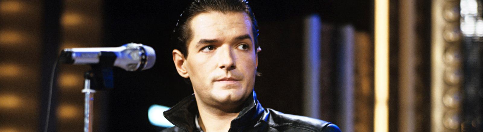 Der Sänger Falco bei einem Auftritt 1985. Er trägt eine schwarze Lederjacke und steht vor einem Mikrofon; Bild: dpa