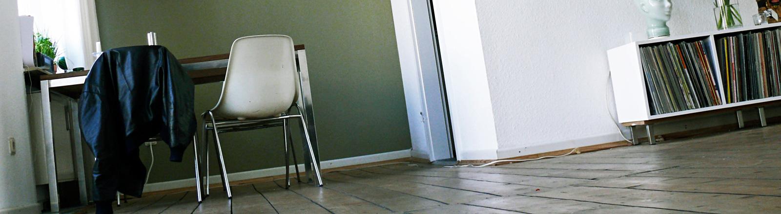 Blick in ein Wohnzimmer. Links steht ein Tisch mit Stühlen. Über einem Stuhl hängt eine Jacke. Rechts steht ein niedriger Schrank mit Schallplatten.