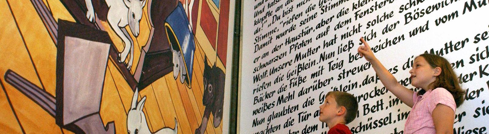 """Vor einem riesigen, aufgeschlagenen Märchenbuch (drei mal vier Meter) stehen ein Junge und ein Mädchen. Links ist eine Szene aus """"Der Wolf und die 7 Geißlein"""" zu sehen, rechts Text; Bild: dpa"""