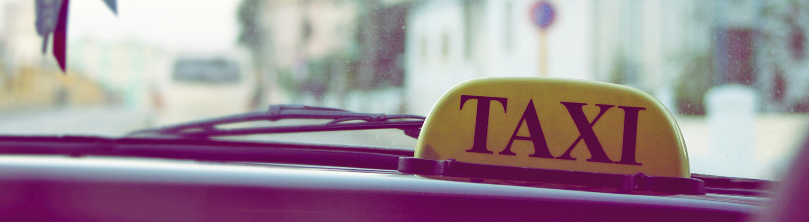 Blick durch die Frontscheibe eines Autos. Ein gelbes Schild, auf dem Taxi steht, steht im Inneren des Autos vor der Scheibe. Außen ist links verschwommen ein Haus zu sehen.