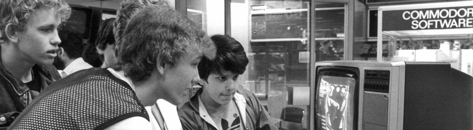 Schwarz-Weiß-Foto. Vier Jungen blicken konzentriert auf einen Röhrenfernseher. Szene in einem Kaufhaus 1984; Bild: dpa