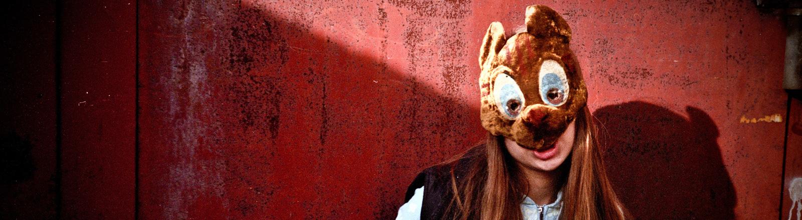 Eine Frau mit langen Haaren trägt eine Maske, ähnlich einem Bären, mit großen Augen und Ohren. Sie steht vor einer roten Wand.