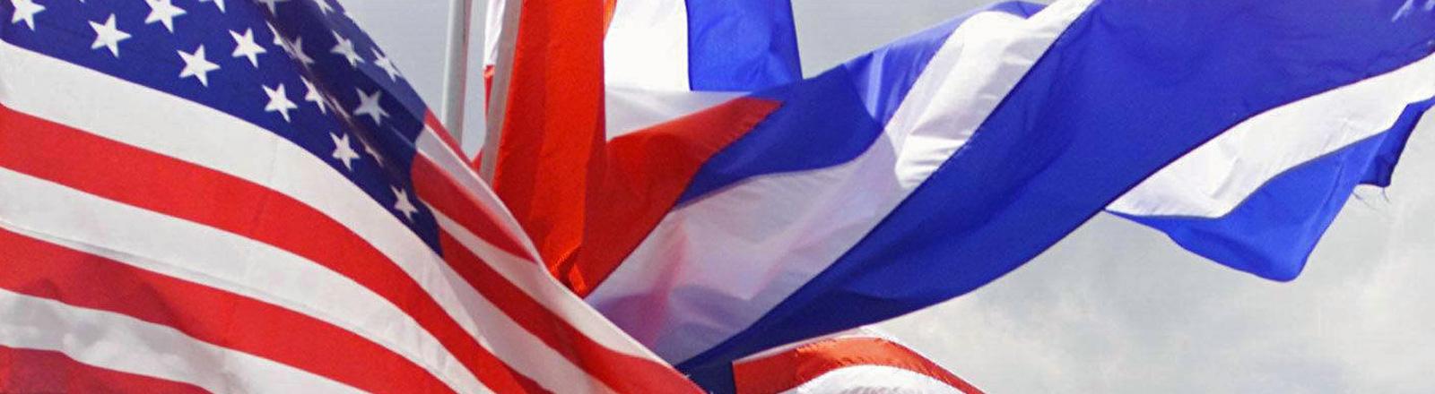 Die US-Flagge und die kubanische flattern durcheinander. Beide sind rot, weiß und blau; Bild: dpa