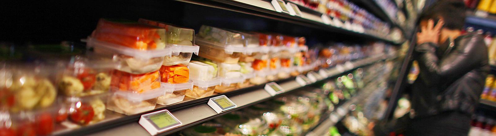 Ein Supermarktregal gefüllt mit Plastikbehältern mit Gemüse. Rechts im Bild steht eine Person, unscharf zu erkennen; Bild: dpa