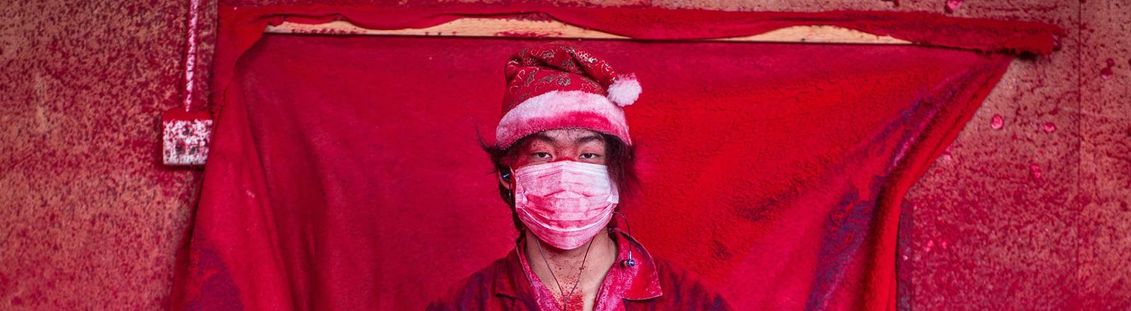 Ein Arbeiter steht mit Weihnachtsmütze bekleidet in einem Raum, der rot von Farbspritzern ist. Links stehen aufgereiht Weihnachtsmännerschuhe als Weihnachtsdeko; Bild: dpa