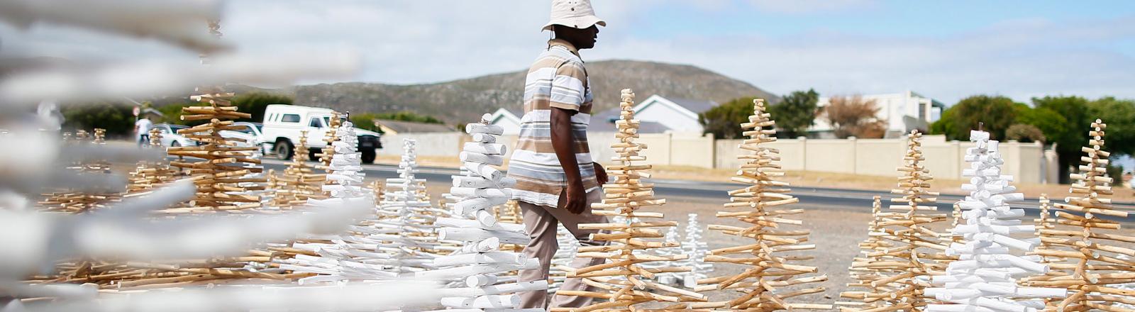 Ein Mann verkauft in Cape Town eine südafrikanische Art von Weihnachtsbäume: Die Bäume werden aus heimischen Holz hergestellt.