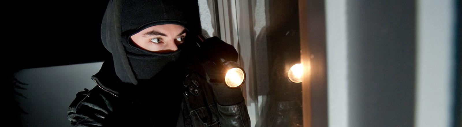 Eine Person, schwarz bekleidet und vermummt steht vor einer Tür und hält eine Lampe in der Hand. Das Bild illustriert eine Einbruchsszene.