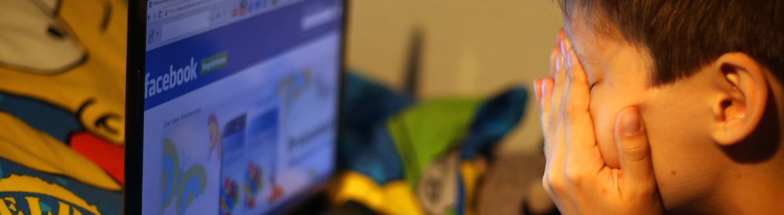 Eine Junge sitzt vor seinem Laptop und hält sich die Augen zu.