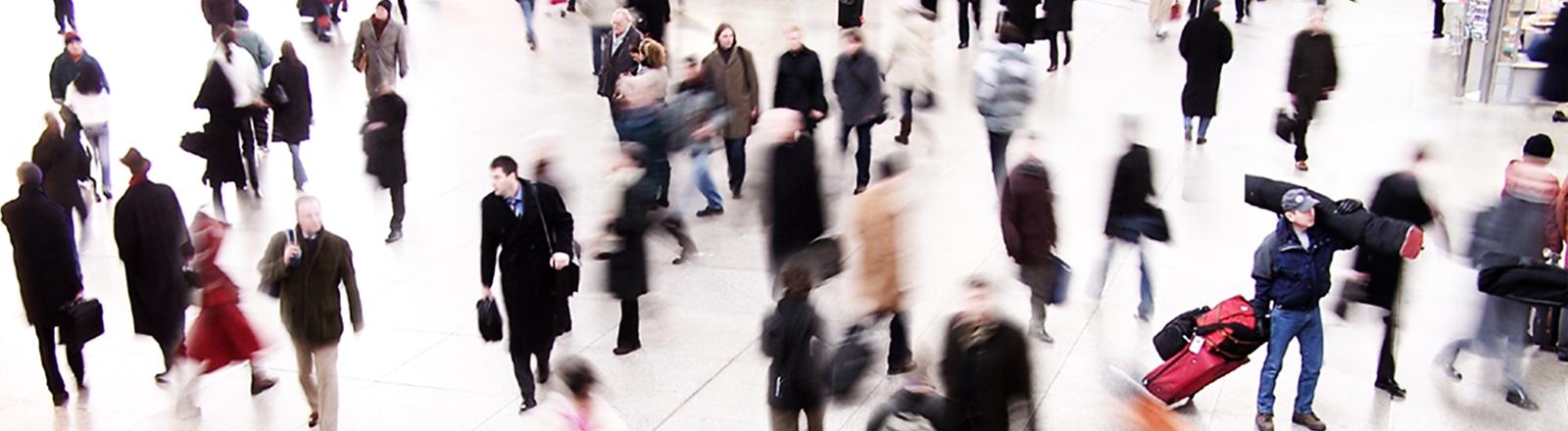 Viele Menschen, zum Teil unscharf fotografiert, von oben auf einem Platz. Crowd.