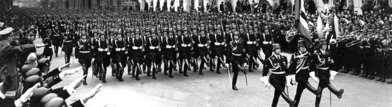 Mitglieder der SS marschieren an Adolf Hitler, der seinen rechten Arm zum Gruß erhoben hat (Bildrand links), vorbei.