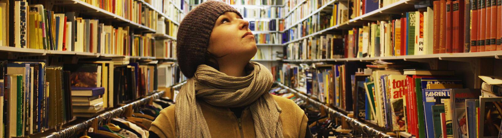 Eine Frau in einer Bibliothek zwischen viele Büchern.