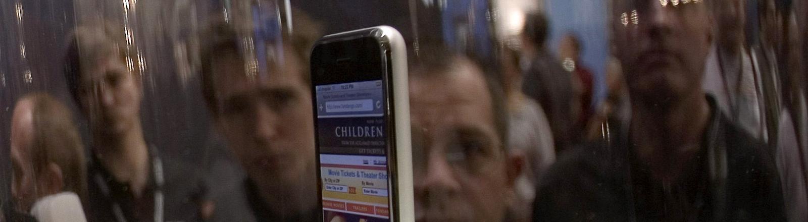 Interessierte betrachten auf der Macworld Expo in San Francisco das in einem Glaskasten ausgestellte ERSTE iPhone am 9. Januar 2007.