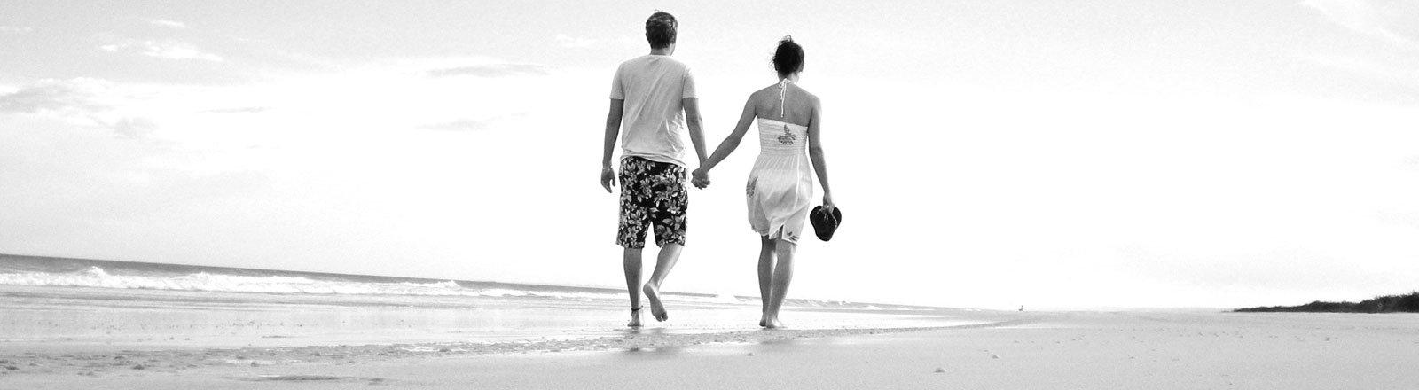 Ein Paar spaziert am Strand entlang.