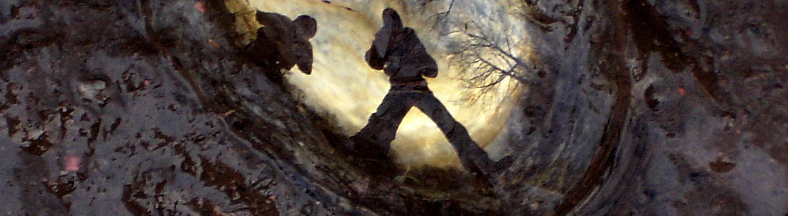 In einer Wasserlache im Schlamm spiegeln sich zwei Menschen