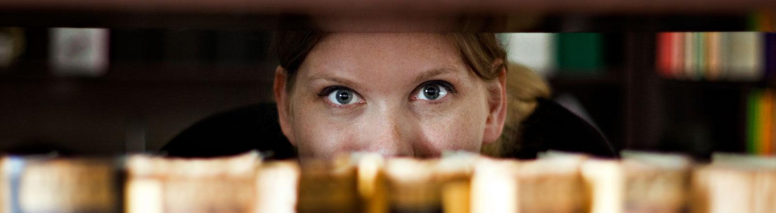 Eine Frau blickt durch ein volles Bücherregal.